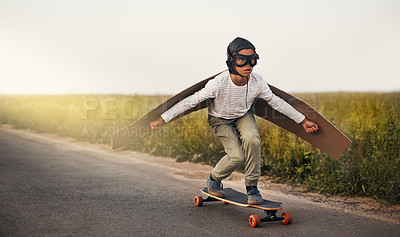 Buy stock photo Shot of a young boy pretending to fly with a pair of cardboard wings while riding a skateboard outside