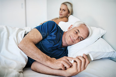 Buy stock photo Shot of a mature man using a cellphone with his wife looking upset in the background at home