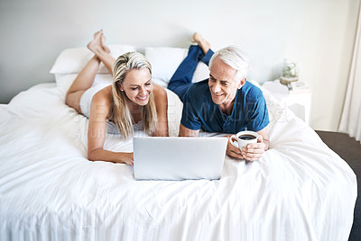 Buy stock photo Shot of a mature couple using a laptop while relaxing on their bed at home