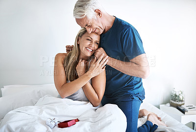 Buy stock photo Shot of a mature man putting a necklace around his wife's neck at home