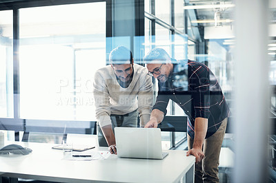 Buy stock photo Shot of two businessmen working together on a laptop in an office