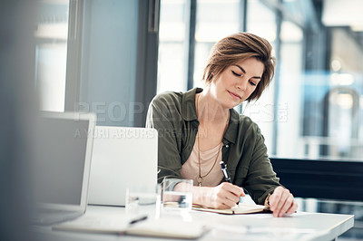 Buy stock photo Shot of an attractive young businesswoman working at her desk in an office