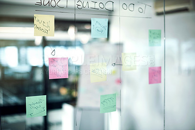 Buy stock photo Shot of sticky notes on a glass wall in an empty office room