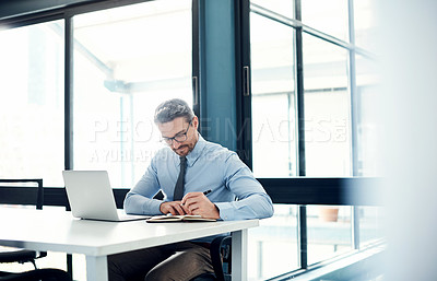 Buy stock photo Shot of a mature businessman making notes at his desk in a modern office
