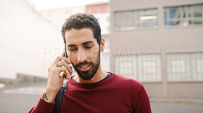 Buy stock photo Cropped shot of a handsome young man on a call and walking in the city