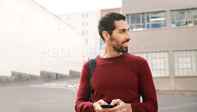Buy stock photo Cropped shot of a handsome young man using a cellphone and walking in the city