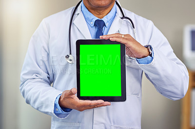 Buy stock photo Shot of an unrecognizable male doctor holding up a digital tablet in front of him while standing inside of a hospital during the day