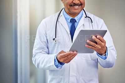 Buy stock photo Shot of an unrecognizable male doctor browsing on a digital tablet inside of a hospital during the day