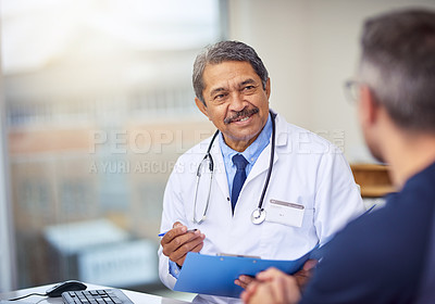 Buy stock photo Shot of a cheerful mature male doctor seated at his desk while consulting a patient inside a hospital during the day