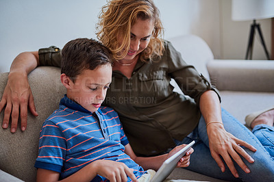 Buy stock photo Cropped shot of a mother and her adorable son using a tablet together on the sofa at home