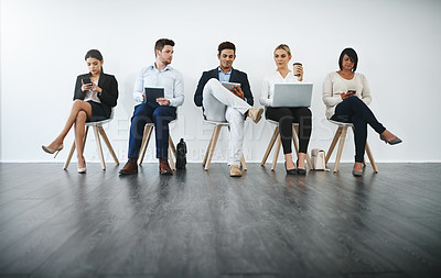 Buy stock photo Full length shot of a group of businesspeople waiting in line for their interviews