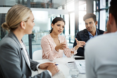 Buy stock photo Shot of an attractive young businesswoman addressing her colleagues during a meeting in the boardroom