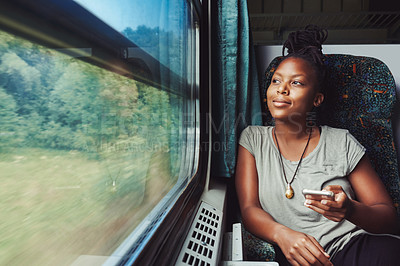 Buy stock photo Cropped shot of a young attractive woman using a cellphone and traveling by train
