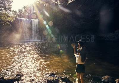 Buy stock photo Shot of a young couple taking photos of a waterfall over a lake