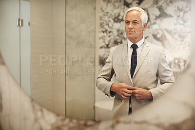 Buy stock photo Shot of an confident mature businessman looking at his reflection in a mirror while getting dressed at home during the day