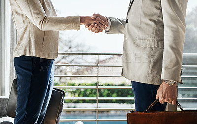 Buy stock photo Shot of two unrecognizable businesspeople shaking hands in agreement inside a house during the day