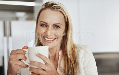 Buy stock photo Portrait of a cheerful middle aged businesswoman seated behind a counter while drinking a cup of coffee inside of a kitchen during the day