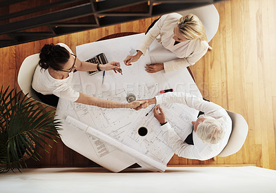 Buy stock photo High angle shot of a group of architects working together on blueprints of a house around a table while shaking hands in agreement inside of a building