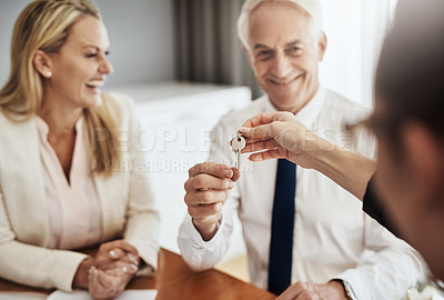 Buy stock photo Shot of a cheerful mature couple receiving keys from a real estate agent to their new house while being seated around a table