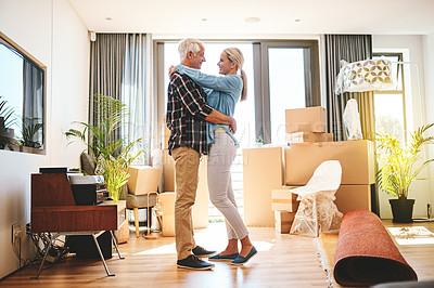 Buy stock photo Shot of a happy mature couple embracing on moving day