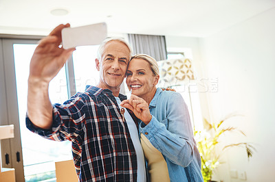 Buy stock photo Shot of a happy mature couple taking a selfie on moving day