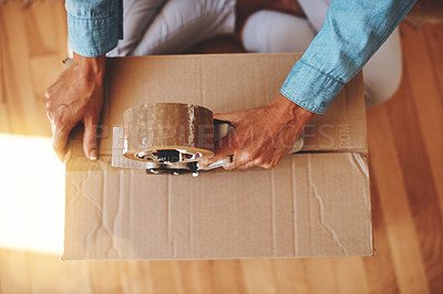 Buy stock photo Cropped shot of a woman sealing a box with adhesive tape at home