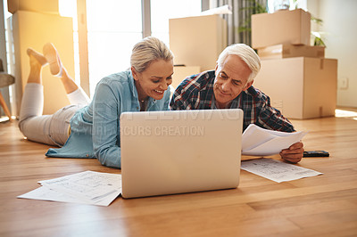 Buy stock photo Shot of a mature couple using a laptop and going through paperwork together on moving day