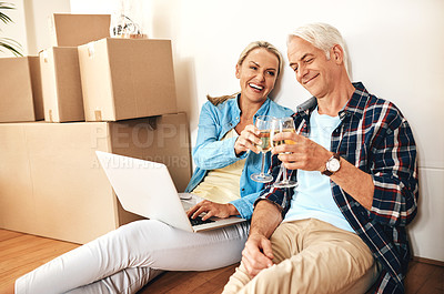 Buy stock photo Shot of a happy mature couple using a laptop and drinking wine together on moving day