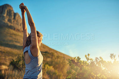 Buy stock photo Shot of a young woman stretching before a run outdoors