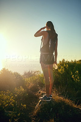 Buy stock photo Shot of a young woman admiring the view from the top of a mountain