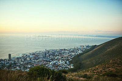 Buy stock photo Shot of the view of a city along the ocean from a mountain peak