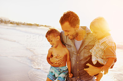 Buy stock photo Shot of a young man and his adorable sons having fun at the beach