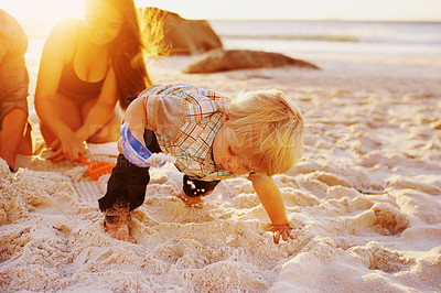 Buy stock photo Shot of an adorable little boy playing in the sand at the beach