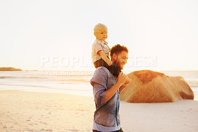 Buy stock photo Shot of a young man carrying his son on his shoulders during a fun day at the beach