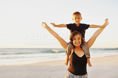 Buy stock photo Shot of a young woman carrying her son on her shoulders during a fun day at the beach
