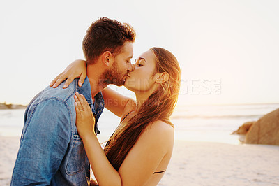 Buy stock photo Shot of an affectionate young couple at the beach