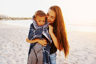 Buy stock photo Shot of a mother lovingly wrapping her son in a towel at the beach