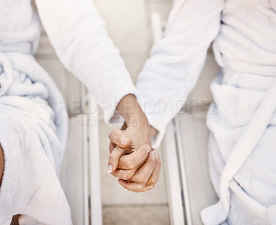 Buy stock photo Shot of two unrecognizable people holding hands while relaxing in bathrobes outside at a spa during the day
