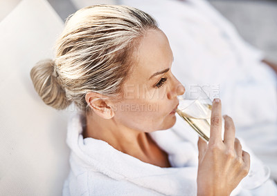 Buy stock photo Shot of a cheerful middle aged woman relaxing on a deckchair while enjoying a glass of champagne outside at a spa during the day