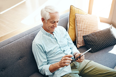 Buy stock photo Cropped shot of a senior man relaxing and using a tablet on the sofa at home