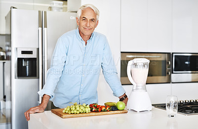 Buy stock photo Cropped portrait of a handsome mature man preparing a healthy nack at home