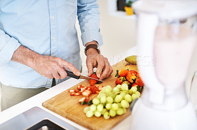 Buy stock photo High angle shot of an unrecognizable mature man preparing a healthy snack at home