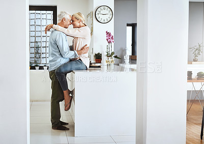 Buy stock photo Full length shot of an affectionate mature couple sharing an intimate moment in their kitchen