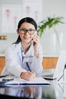 Buy stock photo Cropped portrait of a young female doctor making notes while working in a hospital