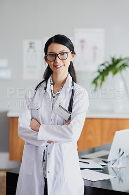 Buy stock photo Cropped portrait of a young female doctor standing with her arms folded in a hospital