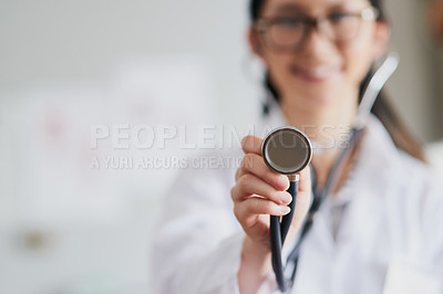 Buy stock photo Cropped shot of a young female doctor reaching out with a stethoscope to listen to your heartbeat