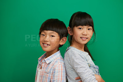 Buy stock photo Studio portrait of two cheerful children standing with their backs against each other next to a green background