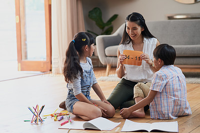Buy stock photo Shot of a cheerful mother and her two children doing homework together while seated on the floor at home during the day