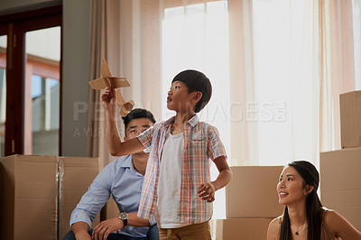 Buy stock photo Shot of a little boy playing with a paper plane at home