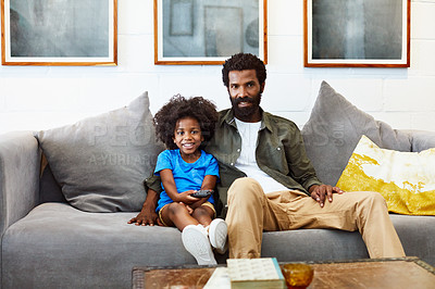 Buy stock photo Portrait of a cheerful young father and son relaxing on a couch while watching television at home